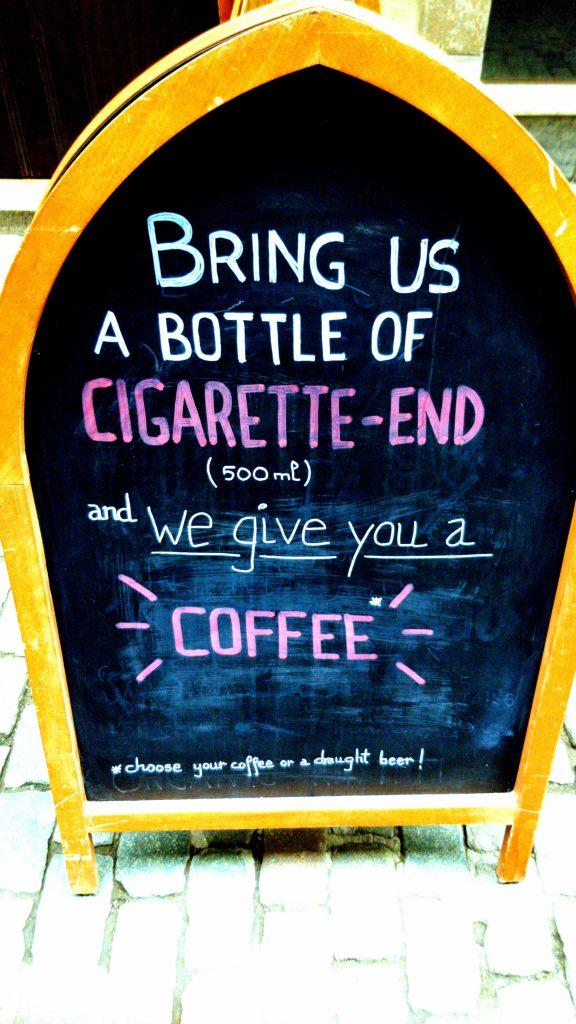 Schild vor dem The Sisters Brussels Café: bringt uns 500 ml Zigarettenkippen und wir geben Euch einen Kaffee aus