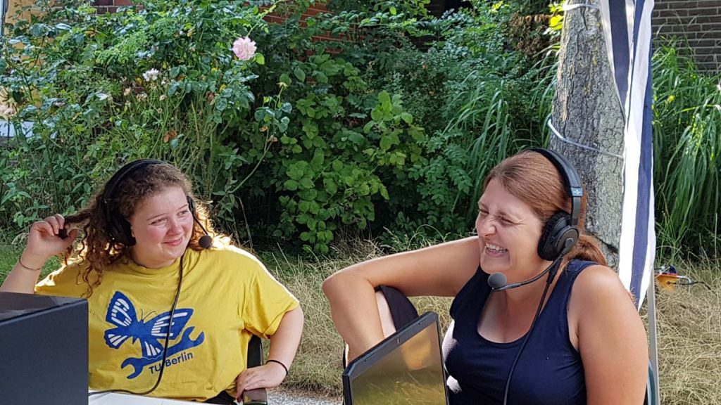 Das Bild zeigt Abby (links) und Gesche. Beide tragen Headsets. Abby wirkt verwirrt, Gesche lacht peinlich berührt. Sie sitzen unter einem blau-weißen Pavillon, von dem man nur eines der Beine sieht. Im Hintergrund ist der Garten der Casa Schaarsa zu sehen.
